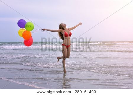 Beautiful Woman In A Swimsuit Enjoying Colorful Balloons On  A Beach At Summer. Concept For Holiday,