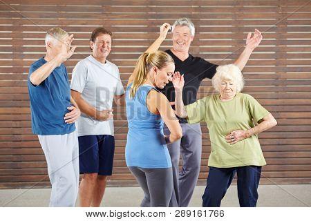 Seniors learn to dance samba in a dance class with a dance teacher