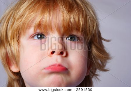 a Young boy pouts at the camera poster