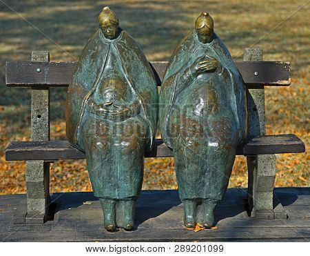 Two Women Marble Figurines Sitting On A Bench