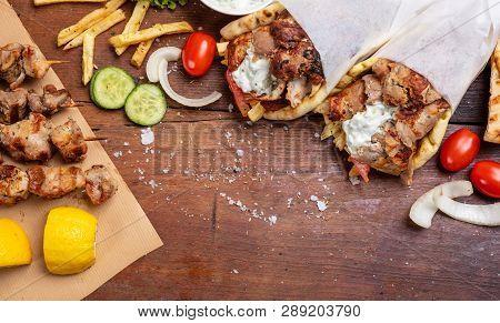 Gyro Pita, Shawarma, Souvlaki. Two Pita Bread Wraps And Meat Skewers On Wooden Table