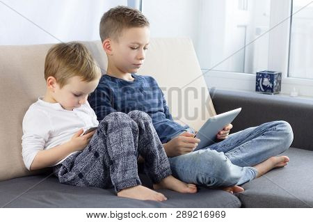 Two Kids Using Tablet Pc And Smartphon At Home. Brothers With Tablet Computer In Light Room. Boys Pl