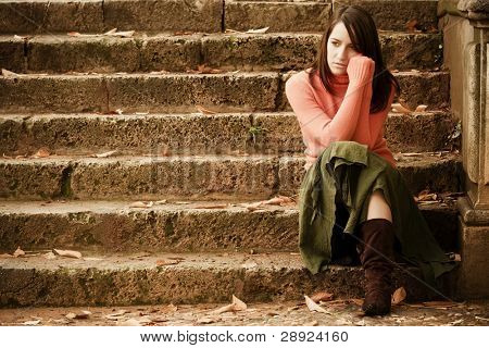 Young thoughtful woman sitting in stone stairs.