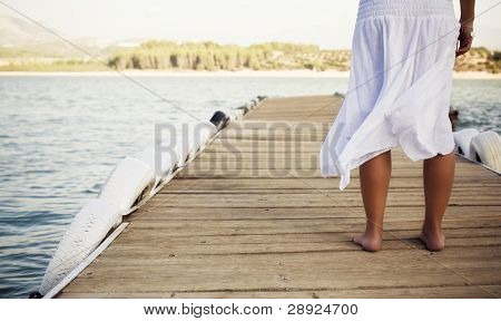 Young shoeless woman on pier . poster