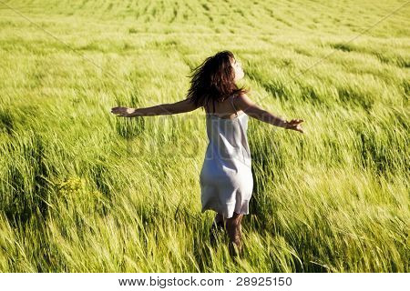 Young beautiful girl feeling freedom in a field.
