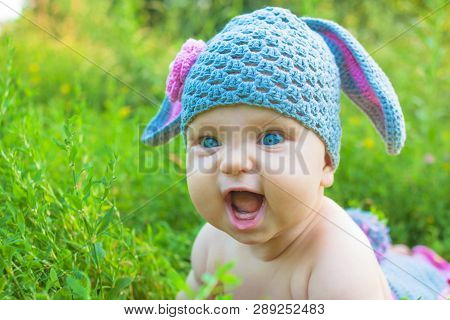Easter Holidays For Happy Kids. Cute Baby In Rabbit Of Lamb Costume In The Green Spring Grass. Smili