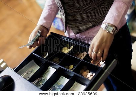 Woman hands on shop cash register. Euro bills and coins.