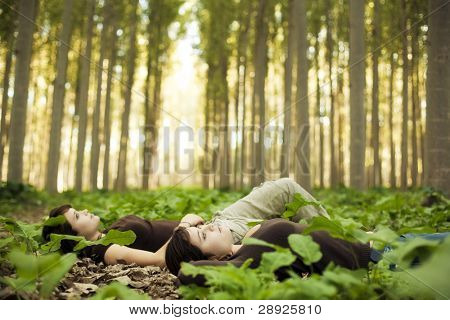 Young beautiful thoughtful girls laying on the ground. Focus on the closest one.