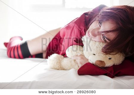 Young beautiful girl and her teddy bear on the bed.
