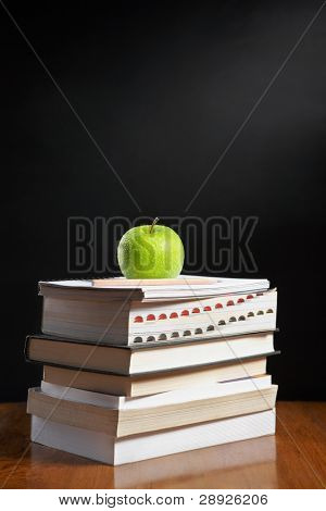 Green apple over pile of books for shool concept