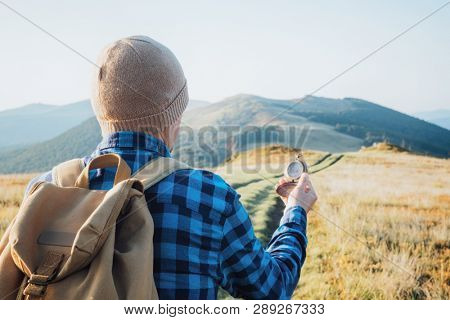 Tourist with compass in hand on mountains road. Travel concept. Landscape photography