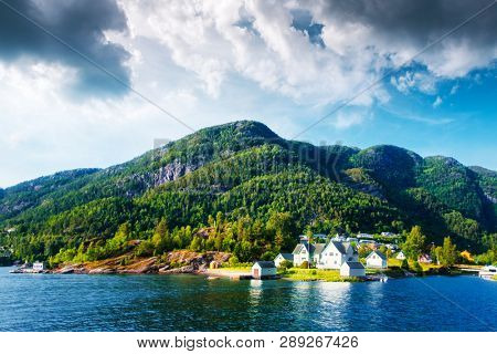 Typical norwegian landscape with small village on fjord coast