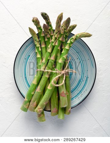 Green asparagus sprout on blue plate top view. Food photography