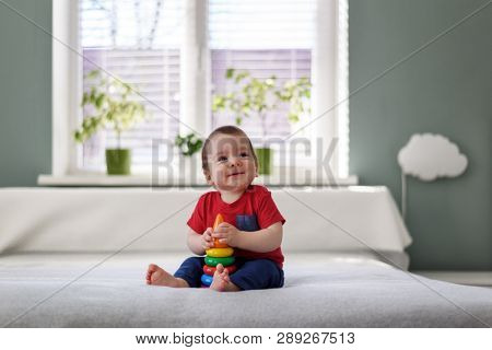 Happy kid with coloured pyramid toy on white bed in his room