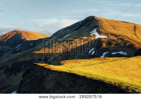 View of the grassy hills in Carpathian mountains glowing by evening sunlight. Dramatic spring scene. Landscape photography