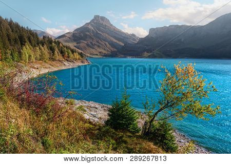 Sunny day on Roselend lake (Lac de Roselend) in France Alps. Blue water and high mountains in background. Landscape photography