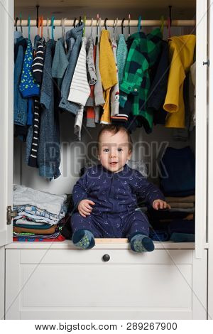 Smiling kid hiden in clothing closet filled with coloured clothes