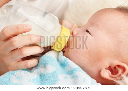 baby is feeding milk from baby's bottle