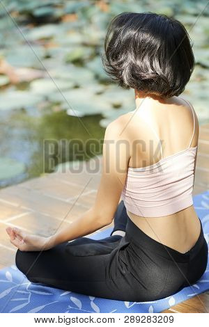 Young Woman Sitting On Yoga Mat By Pond And Enjoying Morning Meditation