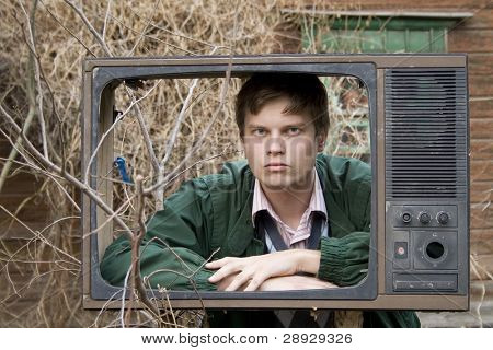 serious man in old tv box, on street