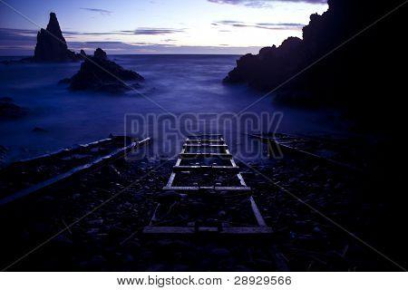 Surreal scene, three railroads straight into the ocean.