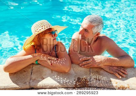 Senior Couple Relaxing In Swimming Pool. People Enjoying Summer Vacation. All Inclusive.