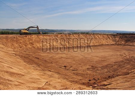 Crawler excavator on the edge of a large excavation. Building a large water tank. poster