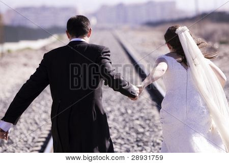 Unrecognizable just married couple running away