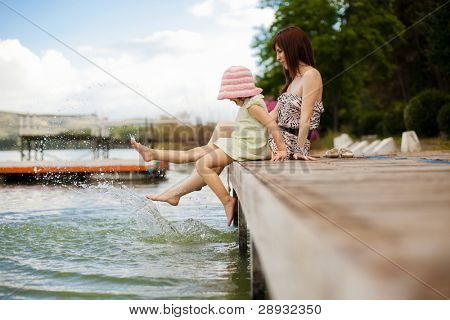 Young mother and her daughter splashing in the lake