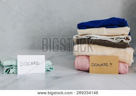 decluttering and tidying up concept: piles of tshirts and clothes being sorted into Keep Discard and Donate categories poster