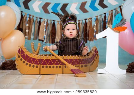 Little cute girl in costume of Apache Indian chief and in a feather headdress sits in canoe. Childrens holiday First birthday and smash cake 1 year poster