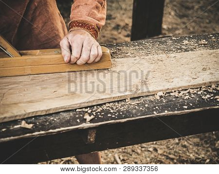 Carpenter In Medieval Cotton Clothes Working With A Wood By Plane. Man Manually Hews A Wooden Board