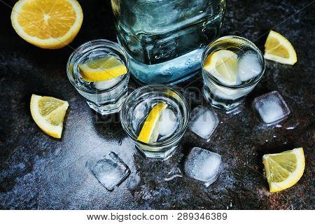 Vodka. Shots, Glasses With Vodka And Lemon With Ice .dark Stone Background.