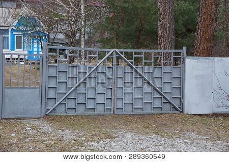 Gray Metal Gates And Part Of The Fence Outside In Dry Grass