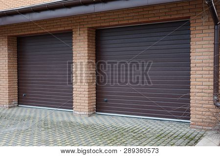 Brick Garage Facade With Two Brown Gates In The Street