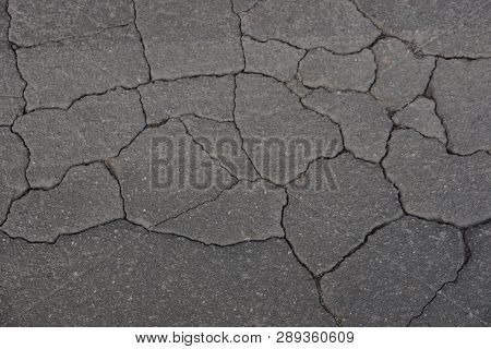 Gray Stone Background Of Old Asphalt In Cracks In The Road