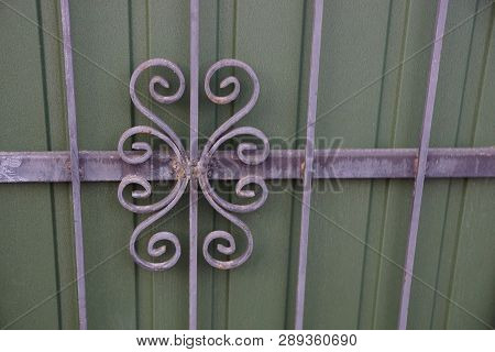 Metal Texture Of Gray Iron Bars In A Forged Pattern On A Green Wall