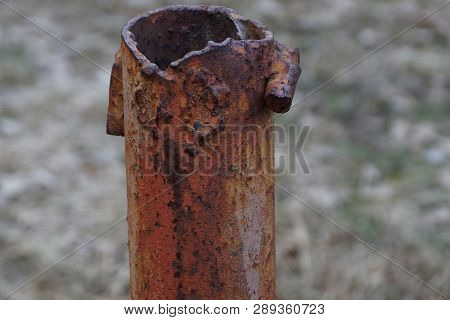 Part Of A Long Rusty Brown Pipe On A Street Pillar