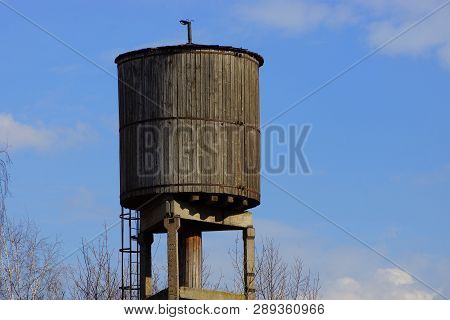 Old Gray Wooden Water Tower Against A Blue Sky And Clouds