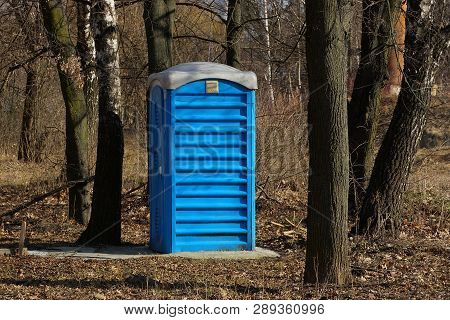 Big Blue Plastic Toilet Stands Among The Trees In The Park