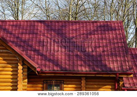 Roof Of A Building With Red Tiles Against The Sky And Branches