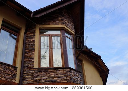 One Large Window On A Brown Stone Attic Wall
