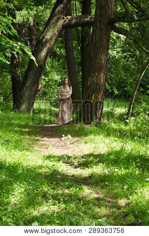 Woman In Vintage Dress Walking Through The Alley Of The Old Park
