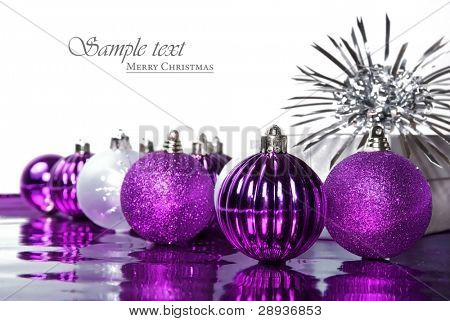Pink christmas baubles against a white background with space for text