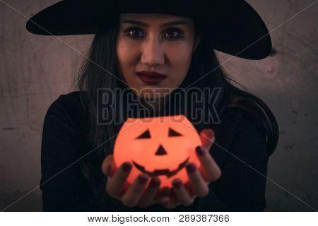 The Witch In Hand Has Halloween Pumpkin On Dark Background, Halloween Day Concept