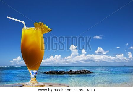 a Lovely cold fresh fruit cocktail with pineapple and straw on a tropical island beach