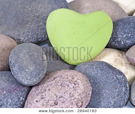 a White colored stone heart surrounded by other natural stones