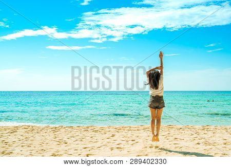 Happy Young Woman In White Shirts And Shorts Jumping At Sand Beach. Relaxing And Enjoying Holiday At
