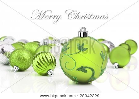 Green christmas decorations on a white background with space for text