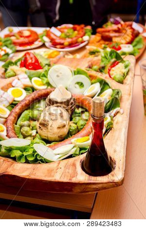 Decorated sausages with fresh vegetables and glass of wine are exposed on traditional sausage tournament. poster